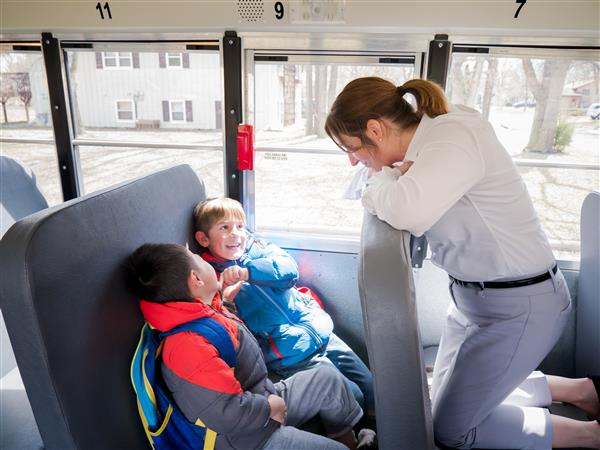 Dr.Baker with preschoolers on a school bus