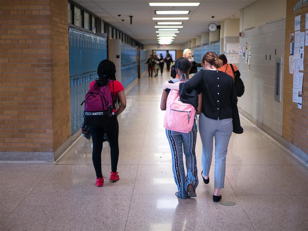 Dr Baker Walking With Students down Brooklyn Center High school Hallways
