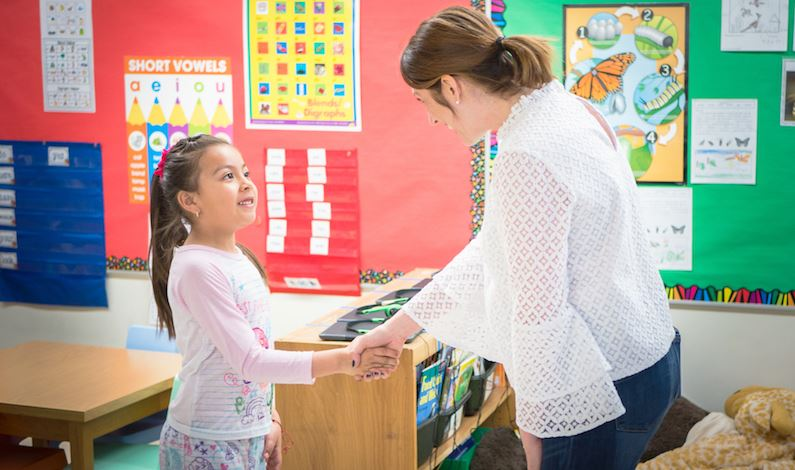 Dr. Baker shaking a first grader's hand